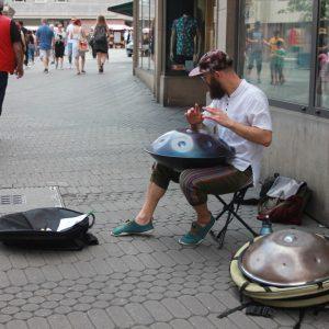 Handpan Musiker spielt in der Fußgängerzone vor Laden-Schaufenster