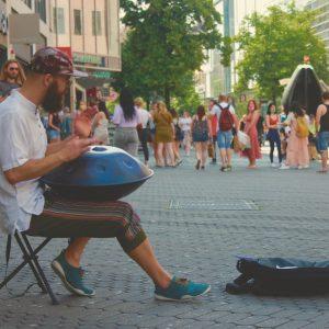 Handpan Musiker spielt Straßenmusik passanten hören zu und genießen die Klänge.