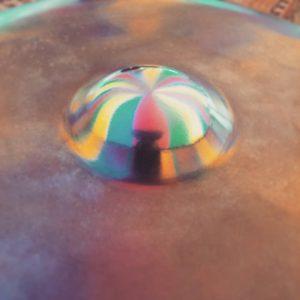 Musiker spiegelt sich in dem Ding seiner Handpan. Die Farben des Zeltes in dem der Auftritt ist, spiegeln sich auch.